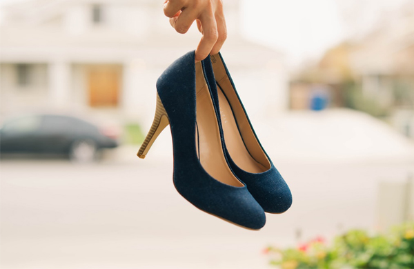 Hand Holding A Pair Of Blue High Heel Shoes
